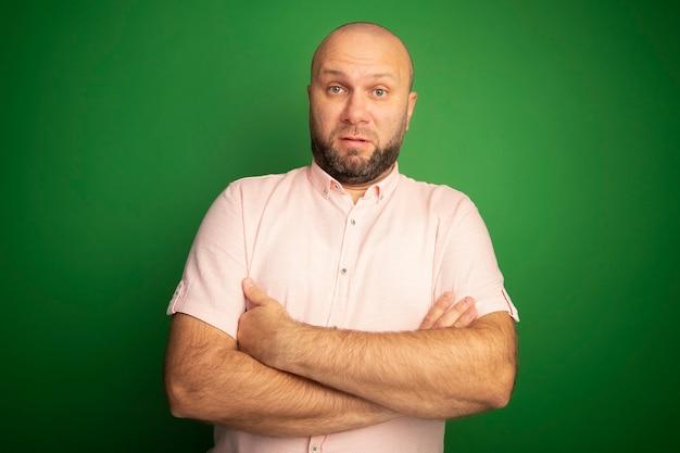 ピンクのtシャツを着て手を組んで驚いた中年ハゲ男