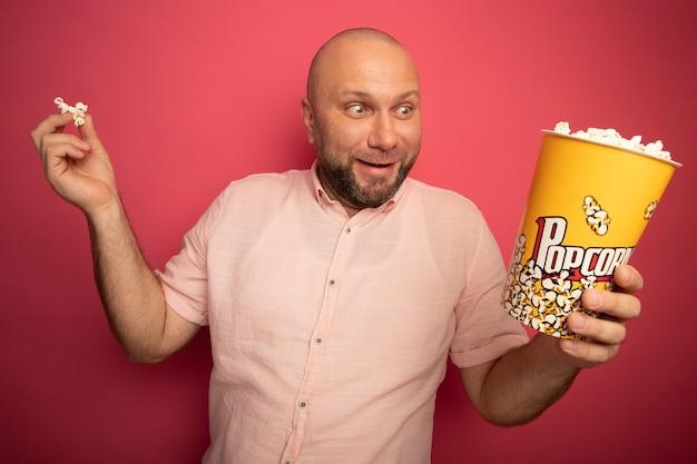 Uomo calvo di mezza età sorpreso che indossa la maglietta rosa che tiene il secchio di popcorn con la pace del popcorn isolata sulla parete rosa