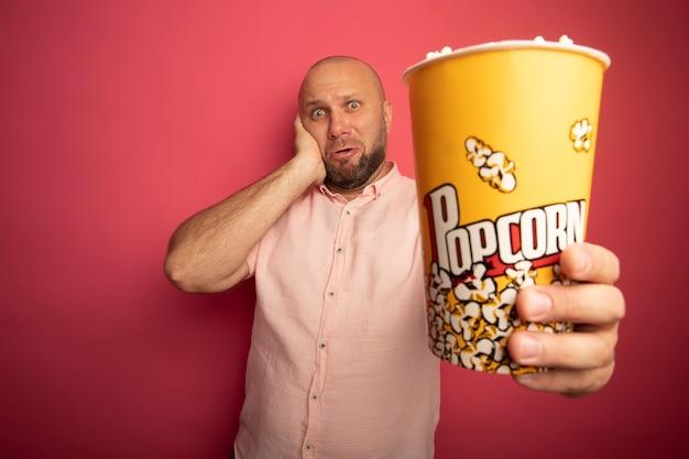 분홍색 벽에 고립 된 뺨에 손을 넣어 팝콘 양동이를 들고 분홍색 티셔츠를 입고 놀란 중년 대머리 남자