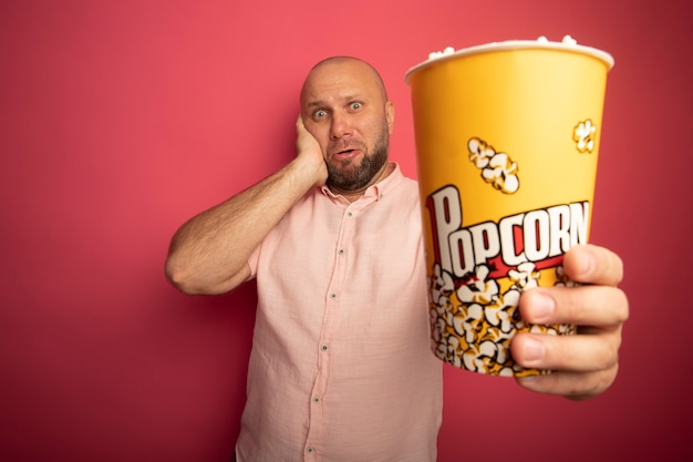 Surprised middle-aged bald man wearing pink t-shirt holding out bucket of popcorn  putting hand on cheek isolated on pink wall