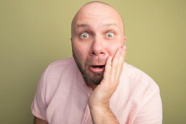 Uomo calvo di mezza età sorpreso che indossa la maglietta rosa che mette la mano sulla guancia