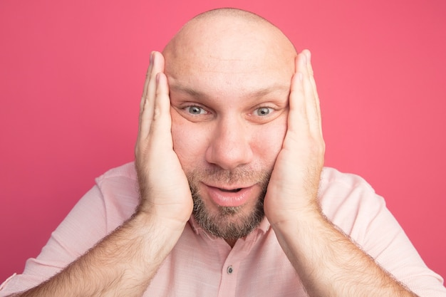 Surprised middle-aged bald man wearing pink t-shirt putting hands on cheeks