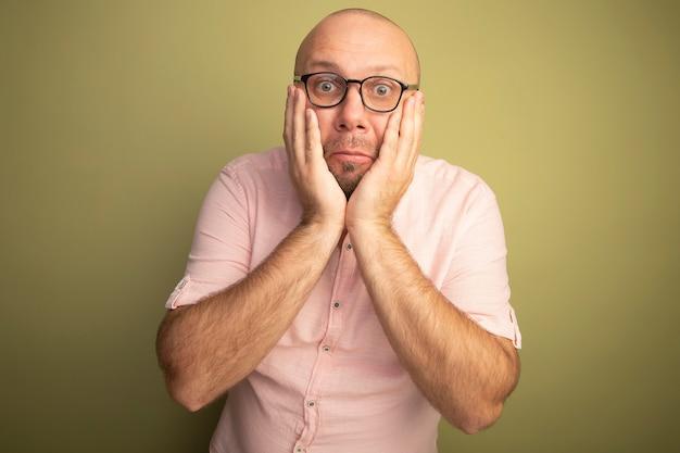올리브 그린에 고립 된 안경 분홍색 티셔츠를 입고 놀란 중년 대머리 남자