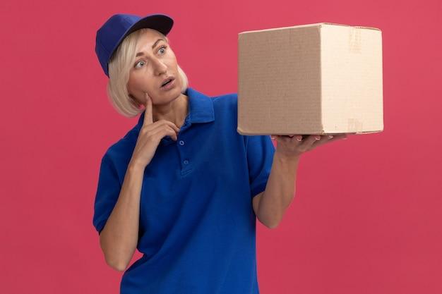 Donna di consegna bionda di mezza età sorpresa in uniforme blu e berretto che tiene e guarda la scatola di cartone mettendo il dito sul viso isolato sul muro rosa