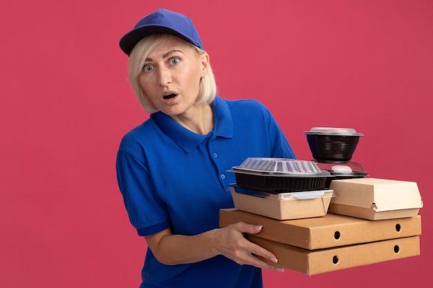 Sorpresa bionda di mezza età donna di consegna in uniforme blu e berretto che tiene pacchetti di pizza con contenitori per alimenti e pacchetto di cibo di carta su di loro guardando davanti