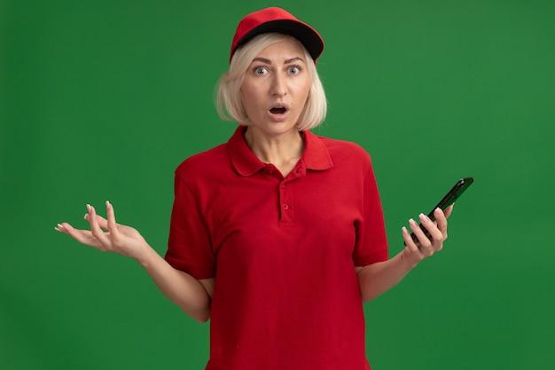 Sorpresa bionda di mezza età donna di consegna in uniforme rossa e cappuccio che tiene il telefono cellulare che mostra la mano vuota isolata sul muro verde