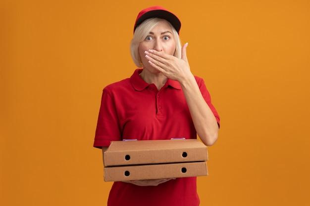 Sorpresa bionda di mezza età consegna donna in uniforme rossa e berretto che tiene i pacchetti di pizza tenendo la mano sulla bocca