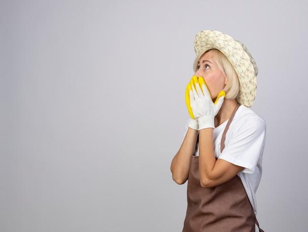 Sorpresa giardiniera bionda di mezza età donna in uniforme che indossa cappello e guanti da giardinaggio in piedi in vista di profilo tenendo le mani sulla bocca alzando lo sguardo isolato sul muro bianco con spazio di copia
