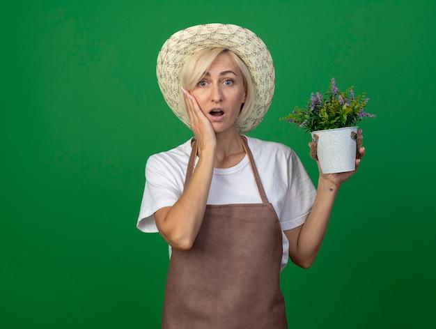 Sorpresa giardiniera bionda di mezza età donna in uniforme che indossa un cappello con un vaso di fiori che tiene la mano sul viso