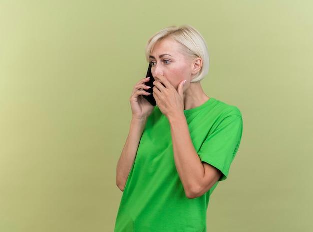 コピースペースのあるオリーブグリーンの壁に隔離された口に手を置いて電話で話している縦断ビューに立っている驚いた中年金髪スラブ女性