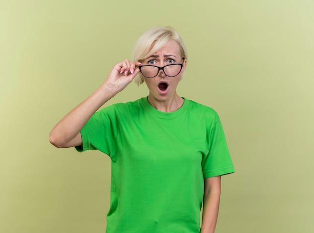 Sorpresa di mezza età bionda donna slava con gli occhiali afferrandoli guardando la telecamera isolata su sfondo verde oliva con spazio di copia