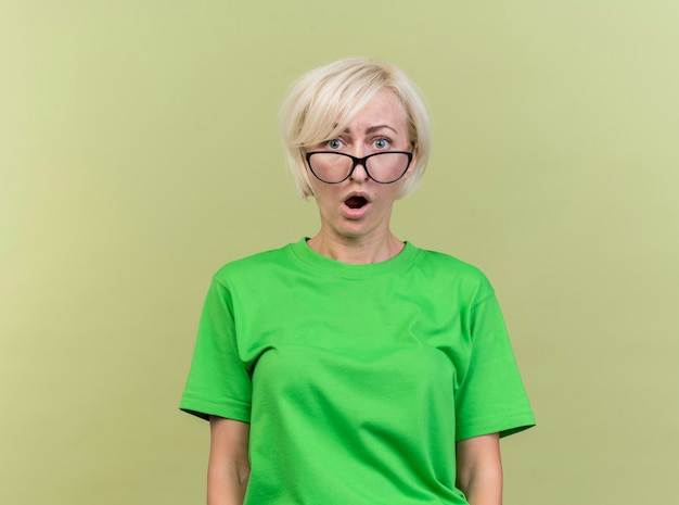 Donna slava bionda di mezza età sorpresa con gli occhiali che guarda l'obbiettivo isolato su priorità bassa verde oliva con lo spazio della copia