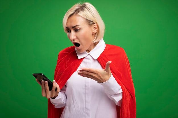 Donna bionda di mezza età sorpresa del supereroe in mantello rosso che tiene e che guarda il telefono cellulare che lo indica con la mano isolata sulla parete verde con lo spazio della copia