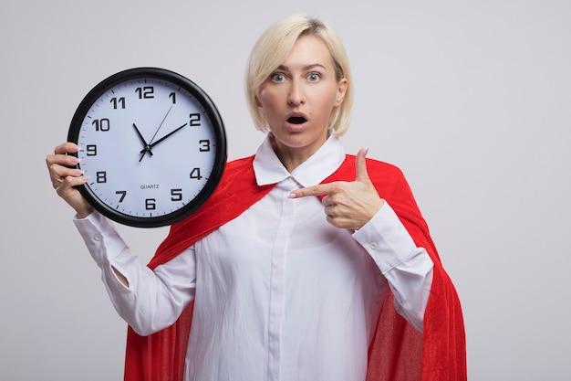 Donna bionda di mezza età sorpresa del supereroe in mantello rosso che tiene e che indica l'orologio isolato sul muro bianco