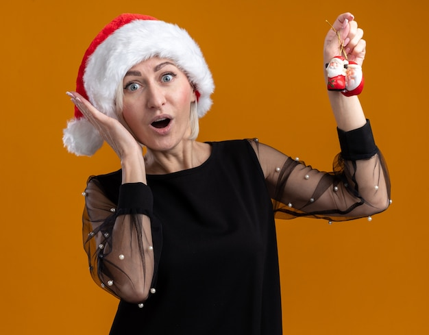 Surprised middle-aged blonde woman wearing christmas hat looking  raising santa claus christmas ornaments keeping hand near head isolated on orange wall