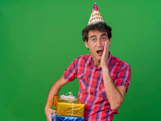 Uomo caucasico di mezza età sorpreso del partito che indossa il cappello di compleanno che tiene confezioni regalo tenendo la mano sul viso che guarda l'obbiettivo isolato su priorità bassa verde con lo spazio della copia