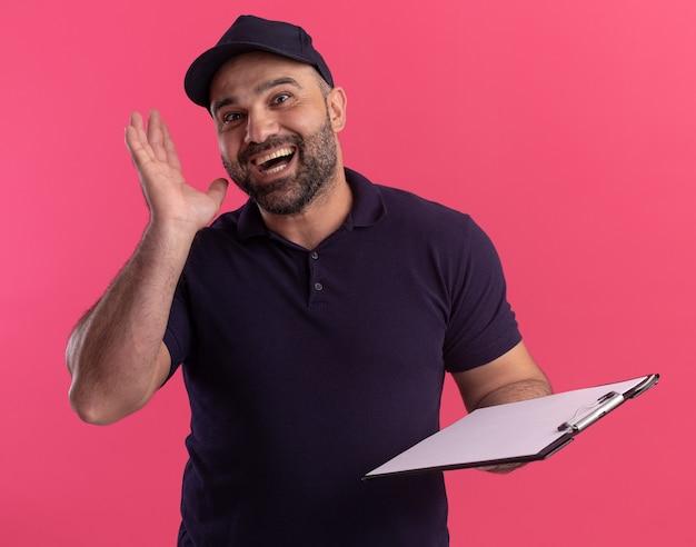유니폼과 모자 핑크 벽에 고립 된 클립 보드를 들고 놀된 중 년 배달 남자