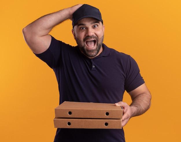 노란색 벽에 고립 된 머리에 손을 넣어 피자 상자를 들고 유니폼과 모자에 놀란 중년 배달 남자