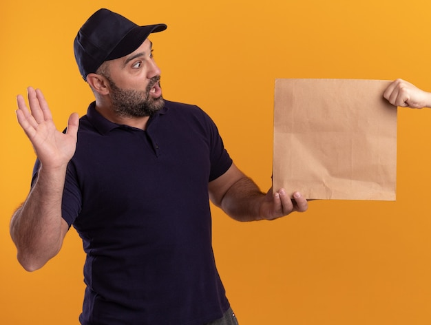 Surprised middle-aged delivery man in uniform and cap giving paper food package to client isolated on yellow wall