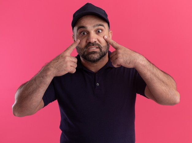 Surprised middle-aged delivery man in uniform and cap pulling down eye lids with fingers isolated on pink wall