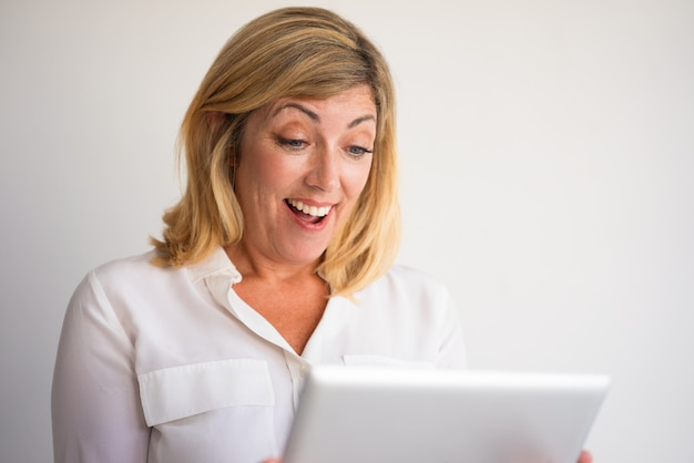 Surprised middle-aged fair-haired woman reading news on tablet computer.