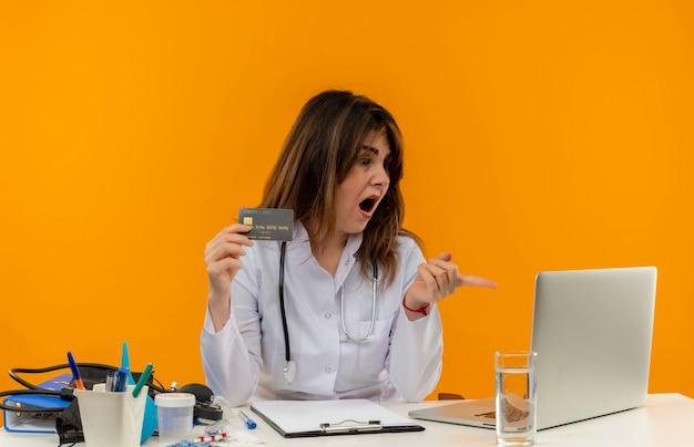 의료 가운과 청진기를 착용하고 의료 도구 클립 보드를보고 고립 된 신용 카드를 들고 노트북을 가리키는 책상에 앉아 놀란 중년 여성 의사