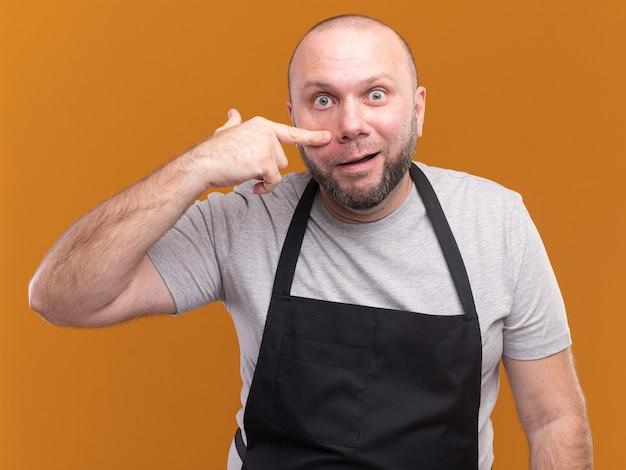Sorpreso barbiere maschio di mezza età in uniforme che tira giù la palpebra isolata sulla parete arancione