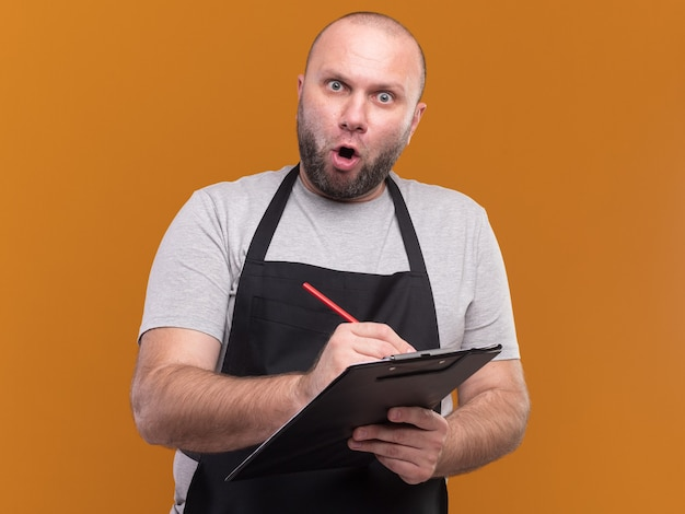 Surprised middle-aged male barber in uniform writing something on clipboard isolated on orange wall