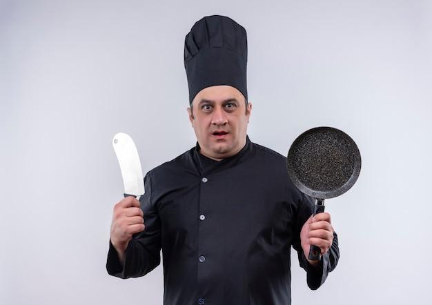 フライパンと包丁を持ったシェフの制服を着た驚いた中年男性料理人