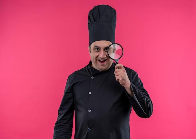 コピースペースで拡大鏡を保持しているシェフの制服を着た驚いた中年男性料理人
