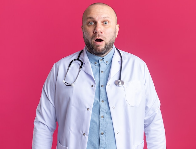 의료 가운과 청진기를 입고 분홍색 벽에 격리된 정면을 바라보는 놀란 중년 남성 의사