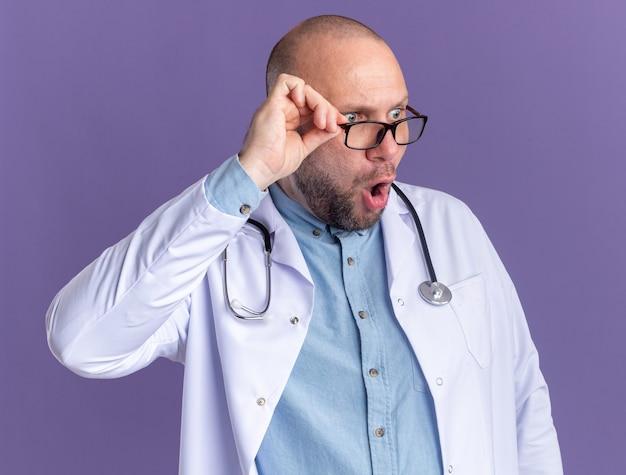 Sorpreso medico maschio di mezza età che indossa accappatoio medico e stetoscopio con occhiali che afferrano gli occhiali guardando il lato isolato sul muro viola