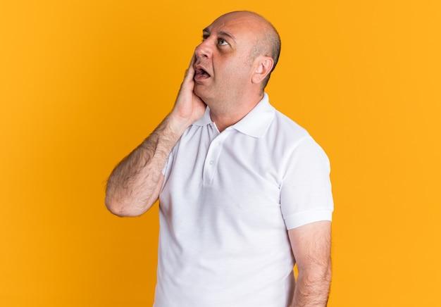 Uomo di mezza età sorpreso che tiene la mano sul viso alzando lo sguardo