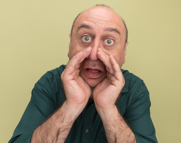 올리브 녹색 벽에 고립 된 사람을 호출하는 녹색 티셔츠를 입고 놀란 중년 남자