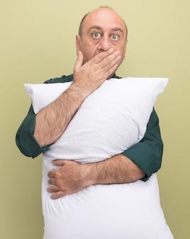 녹색 티셔츠를 입고 놀란 중년 남자가 올리브 녹색 벽에 고립 된 손으로 베개 덮여 입을 안아