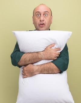 L'uomo di mezza età sorpreso che indossa la maglietta verde ha abbracciato il cuscino isolato sulla parete verde oliva