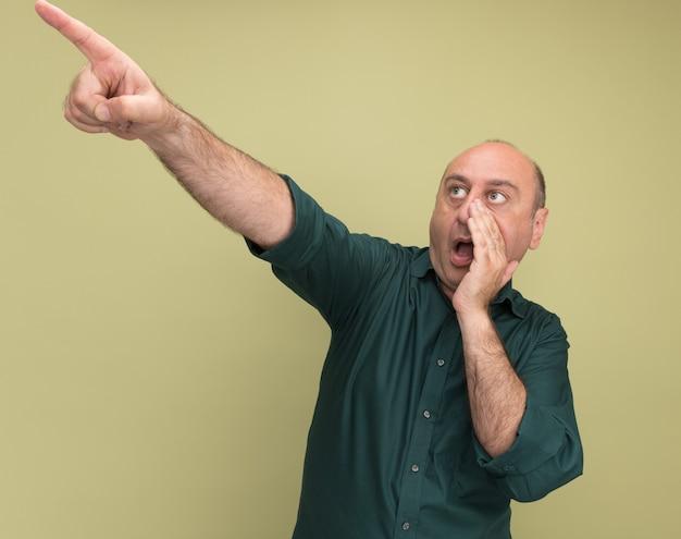 Sorpreso uomo di mezza età che indossa una maglietta verde punta a lato chiamando qualcuno isolato sul muro verde oliva