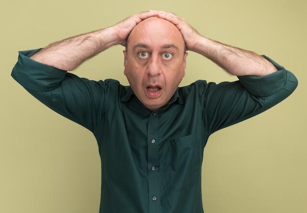 Удивленный мужчина средних лет в зеленой футболке, положив руки за голову, изолирован на оливково-зеленой стене
