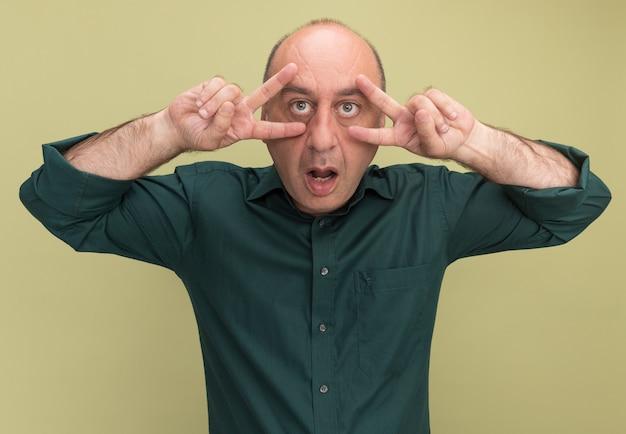 Uomo di mezza età sorpreso che indossa la maglietta verde che mostra gesto di pace isolato sulla parete verde oliva
