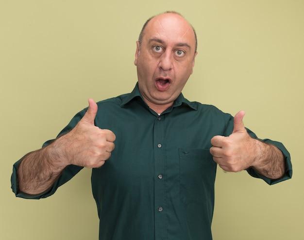 올리브 녹색 벽에 고립 엄지 손가락을 보여주는 녹색 티셔츠를 입고 놀란 된 중년 남자
