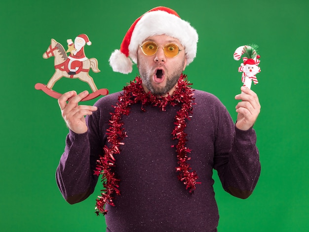 Surprised middle-aged man wearing santa hat and tinsel garland around neck with glasses holding candy cane ornament and santa