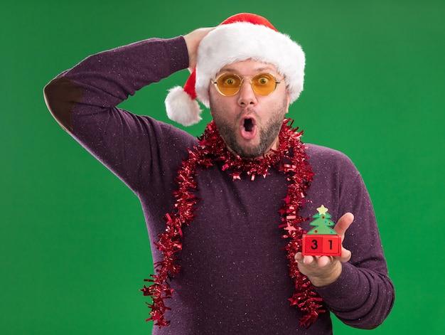 Uomo di mezza età sorpreso che indossa il cappello della santa e la ghirlanda di orpelli intorno al collo con gli occhiali che tengono il giocattolo dell'albero di natale con la data che guarda l'obbiettivo