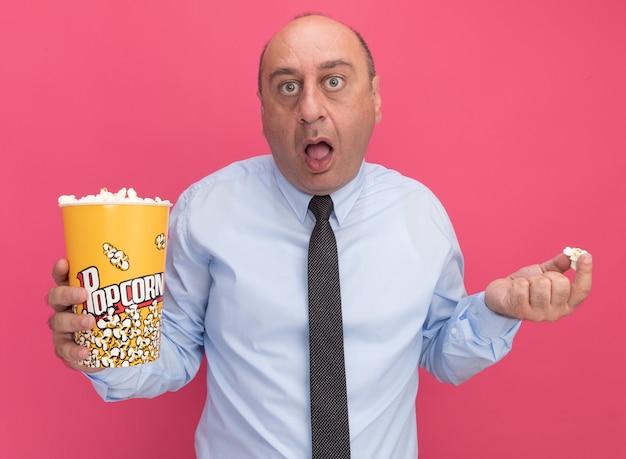 Uomo di mezza età sorpreso che indossa t-shirt bianca con cravatta che tiene secchio di popcorn e pezzo di popcorn isolato sul muro rosa