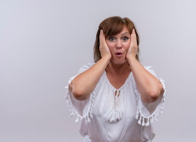 Удивленная женщина средних лет кладет руки на лицо на изолированной белой стене
