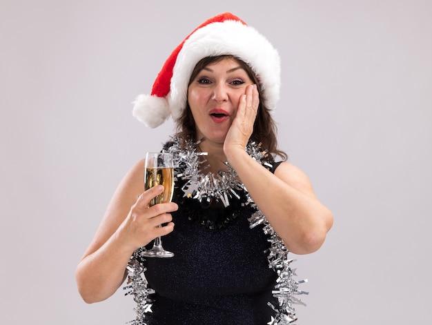 サンタの帽子と見掛け倒しの花輪を首に身に着けている驚いた中年の女性は、白い背景で隔離の顔に手を保ちながらカメラを見てシャンパンのガラスを保持しています