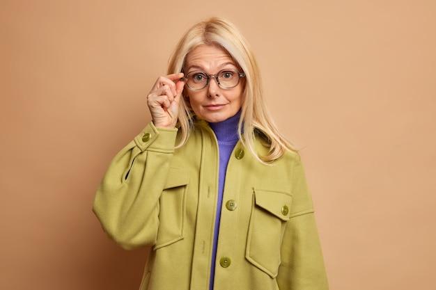 금발 머리를 가진 놀란 중년 여인은 투명한 안경을 통해 궁금해하고 녹색 코트를 입습니다.