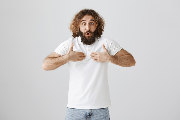 Surprised middle-eastern man pointing at himself