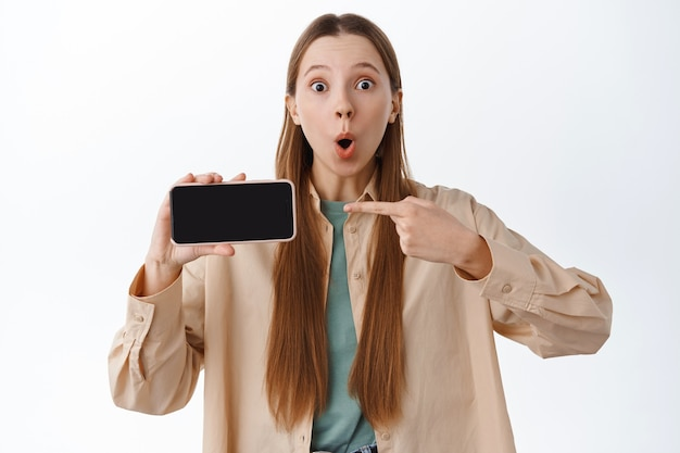 Удивленная миллениальная девушка говорит «вау», указывая на горизонтальный экран смартфона, показывая мобильный дисплей с изумленным лицом, стоя над белой стеной