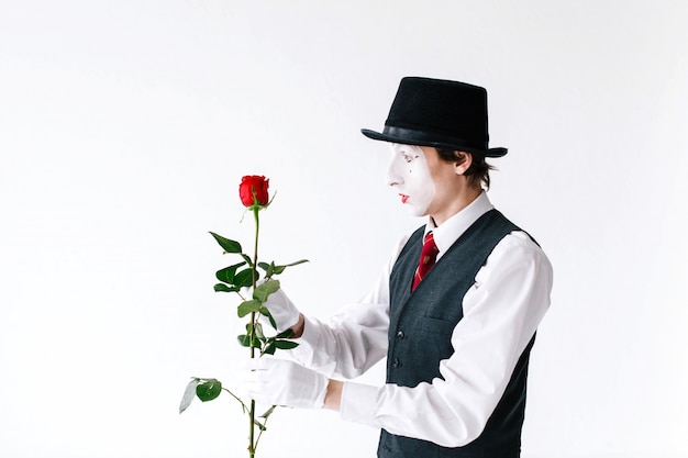 Surprised mime looks at red rose