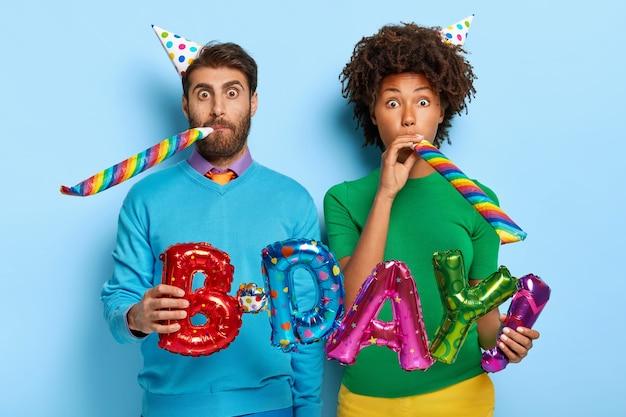 Удивленные женщина и мужчина смешанной расы дуют в рожки вечеринки